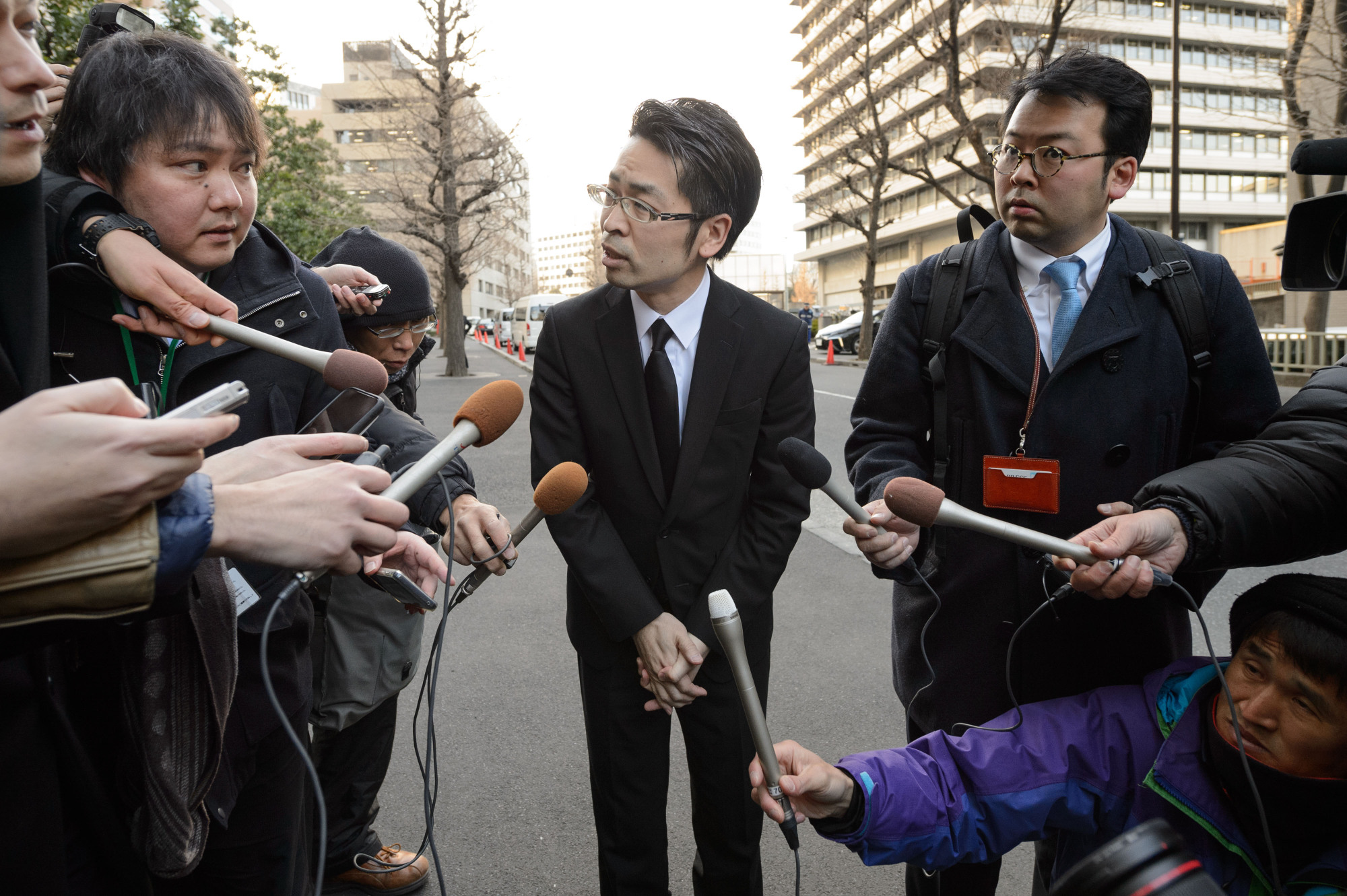 Coincheck Chief Operating Officer Yusuke Otsuka speaks to reporters outside the Financial Services Agency in Tokyo on Feb. 13. Coincheck, which lost ¥58 billion to hackers in January, had to explain to the FSA how the hack occurred and its plans for improving its security. | BLOOMBERG