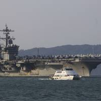 A Vietnamese passenger boat sails past the U.S. aircraft carrier USS Carl Vinson as it docks in Da Nang Bay, Vietnam, on March 5. The Carl Vinson recently completed the first visit to a Vietnamese port since the end of the Vietnam War.   AP