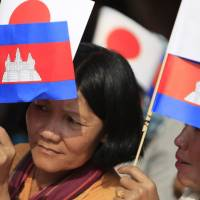 Cambodians hold the flags of Japan and their country as they listen to Prime Minister Hun Sen's speech Tuesday during the inauguration ceremony of a road funded by Japan at Kdey Takoy village, located on the outskirts of Phnom Penh. | AP