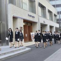 New employees walk to their office in Tokyo on April 1, 2014. Many Japanese organizations maintain a traditional approach to work, including hiring new staff in spring and basing promotions on seniority. | GETTY IMAGES