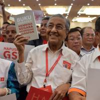 Former Malaysian Prime Minister Mahathir Mohamad, now a prime ministerial candidate, holds an election manifesto by the four-party coalition Pact of Hope on March 8. | AFP-JIJI