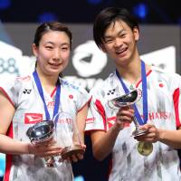 Arisa Higashino (left) and Yuta Watanabe celebrate with their trophies after winning the All England Open mixed doubles title on Sunday in Birmingham, England. | ACTION IMAGES VIA REUTERS