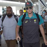 Australia captain Steve Smith arrives with teammates at Cape Town international airport on Tuesday. | AP