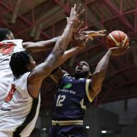 Ryukyu's Hassan Martin takes a shot while being double-teamed by Osaka's Xavier Gibson (left) and Keith Benson in the fourth quarter on Friday night in Okinawa City. The Golden Kings beat the Evessa 78-66. | B. LEAGUE