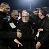 PAOK Thessaloniki  president Ivan Savvidis (center) is escorted off the pitch after running onto it carrying a handgun in his waistband after the referee refused a last-minute goal against visiting AEK Athens on Sunday.