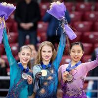 Mako Yamashita shares the podium at the world junior championships in Sofia on Saturday night with gold medalist Alexandra Trusova (center) and silver medalist Alena Kostornaia of Russia. | KYODO