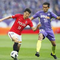 Urawa Reds' Takuya Aoki (left) and Sanfrecce Hiroshima's Teerasil Dangda vie for the ball during the J. League game on Sunday. | KYODO