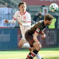 Takashi Usami (left) watches the ball during Fortuna Dusseldorf's 2-1 win over St. Pauli in the German second division on Sunday. | KYODO