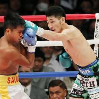 IBF junior featherweight champion Ryosuke Iwasa (right) punches Ernesto Saulong in the first round of their title bout on Thursday at Ryogoku Kokugikan. | KYODO