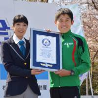 Marathon runner Yuki Kawauchi receives a certificate from Guinness World Records on Sunday recognizing his achievement in completing the highest number of marathons in under 2 hours, 20 minutes. | KYODO