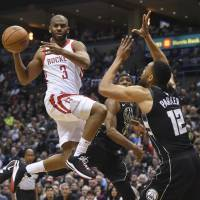Houston's Chris Paul passes the ball as Milwaukee's Jabari Parker defends in the third quarter on Wednesday night. | USA TODAY / VIA REUTERS