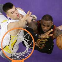 Cavaliers forward LeBron James (right) takes a shot while being defended by the Lakers' Ivica Zubac during the second half on Sunday in Los Angeles.   AP