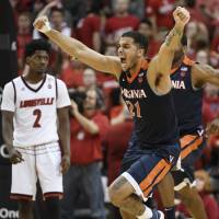 Virginia forward Isaiah Wilkins (21) and guard Kyle Guy and his teammates celebrate after a 67-66 win over Louisville on March 1. The Cavaliers are the No. 1 overall seed for the upcoming NCAA Tournament. | USA TODAY / VIA REUTERS