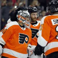Flyers goalie Peter Mrazek (left) celebrates with teammates after Philadelphia's win over the Jets on Saturday. | AP