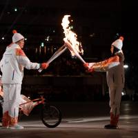 Athletes pass the Paralympics torch during the opening ceremony for the Pyeongchang Winter Paralympics at Olympic Stadium in Pyeongchang, South Korea, on Friday. | REUTERS