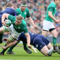 Scotland's Simon Berghan (center) tackles Ireland's Dan Leavy during their Six Nations game in Dublin on Saturday. | AFP-JIJI