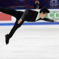 Nathan Chen of the United States soars through the air during the men's free skate at the world championships on Saturday. Chen captured the gold medal with 321.40 points. | AP