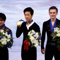 Gold medalist Nathan Chen (center) poses with runner-up Shoma Uno (left) and Russian bronze medalist Mikhail Kolyada at the world championships on Saturday. | REUTERS