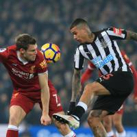 Liverpool's James Milner (left) and Newcastle's Kenedy vie for the ball during their match on Saturday in Liverpool, England. | AFP-JIJI