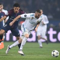 Real Madrid's Karim Benzema (right) moves the ball past Paris Saint-Germain's Marquinhos during their Champions League last-16, second-leg match in Paris on Tuesday. | AFP-JIJI