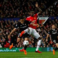Sevilla's Gabriel Mercado (left) competes with Manchester United's Eric Bailly during their Champions League second-round, second-leg match at Old Trafford on Tuesday. | REUTERS