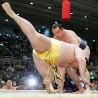 Kakuryu takes down Endo at the Spring Grand Sumo Tournament in Osaka on Monday. | KYODO