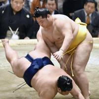 Endo defeats Mitakeumi on Tuesday at the Spring Grand Sumo Tournament in Osaka. | KYODO
