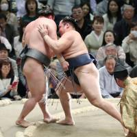 Yokozuna Kakuryu pushes Arawashi out of the ring on the fourth day of the Spring Grand Sumo Tournament in Osaka on Wednesday. | KYODO
