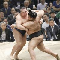 Takayasu (right) pushes Kakuryu out of the ring at the Spring Grand Sumo Tournament in Osaka on Sunday. | KYODO