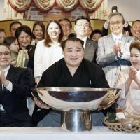 Spring Grand Sumo Tournament champion Kakuryu celebrates with his supporters after the competition on Sunday in Osaka. The Mongolian yokozuna took the title with a 13-2 record. | KYODO
