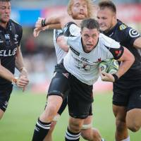 The Sunwolves' Grant Hattingh (center) tries to elude the Sharks' Andre Esterhuizen (right) and Stephan Lewies on Saturday in Durban | AFP-JIJI