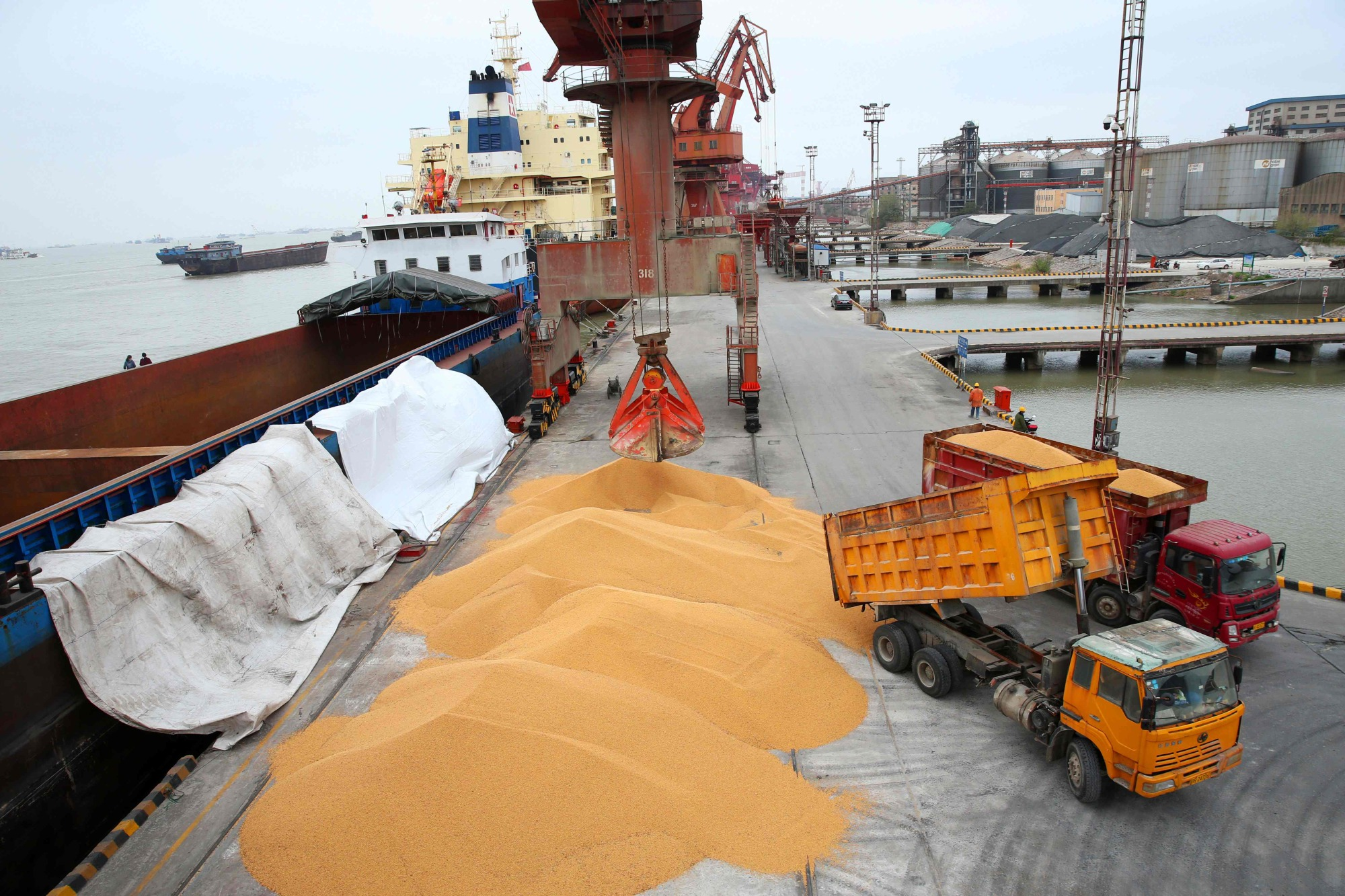 Workers load imported soybeans onto trucks at a port in Nantong in China's eastern Jiangsu province on Wednesday. China unveiled plans Wednesday to hit major U.S. exports worth $50 billion, such as soybeans, cars and small airplanes, with retaliatory tariffs in an escalating trade duel between the world's two top economies. | AFP-JIJI
