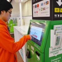 A visitor uses a currency converter at Haneda airport in Tokyo on Jan. 19. | KYODO