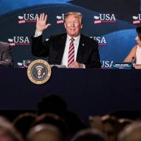 U.S. President Donald Trump waves while sitting next to Maximo Alvarez (left), president of Sunshine Gasoline Distributors, and Irina Vilarino, owner of Las Vegas Cuban Cuisine, during roundtable discussion on tax cuts for Florida small businesses in Hialeah, Florida, Monday. Trump accused China and Russia of devaluing their currencies, breaking from his own Treasury chief's view that no major trading partners are currency manipulators. | BLOOMBERG