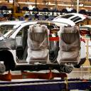Assembly line worker Melvin Matthews uses a large robotic machine to install front seats in a new 2009 Chevrolet Traverse at the GM Spring Hill Manufacturing Plant, in Spring Hill, Tennessee, in 2008. General Motors is adding a shift at the Tennessee factory that makes GMC and Cadillac SUVs, putting about 700 people to work.