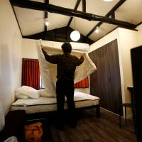 Yasuhiro Inaoka, who manages apartments for owners who provide short-term lodging services, arranges a bed after guests checked out at a Tokyo apartment that is listed on Airbnb. | REUTERS