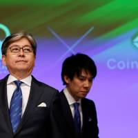 Monex Group Inc CEO Oki Matsumoto (left) and Coincheck CEO Koichiro Wada attend a joint news conference in Tokyo on Friday. | REUTERS