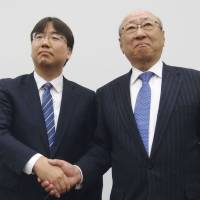 Shuntaro Furukawa (left) and Tatsumi Kimishima attend a news conference in Osaka on Thursday. | BLOOMBERG