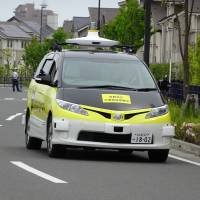 A self-driving delivery vehicle moves down a closed-off street during an experiment by Yamato Transport Co. and DeNA Co. in Fujisawa, Kanagawa Prefecture, on Tuesday. | KAZUAKI NAGATA