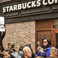 Tsehaitu Abye holds up a banner as people demonstrate outside a Starbucks cafe in PhiladelphiaSunday in this picture obtained from social media. | TWITTER / @JILLIANPHL /VIA REUTERS