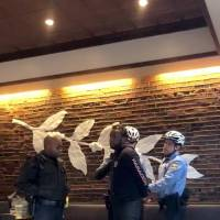 Police detain a man inside a Starbucks cafe in Philadelphia Thursday in this picture grab obtained from social media video. | MELISSA DEPINO / VIA REUTERS