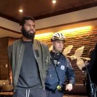 Police officers detain a man inside a Starbucks cafe in Philadelphia on Thursday in this screenshot obtained from video posted to social media. | REUTERS