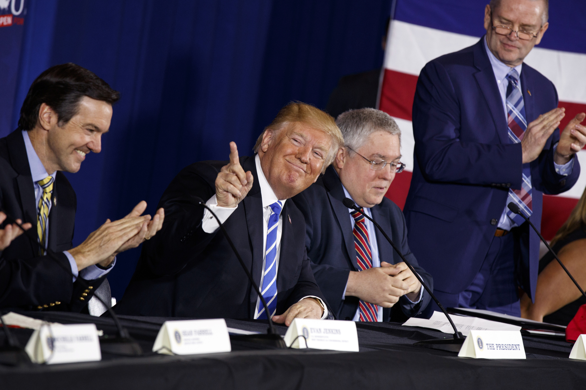 President Donald Trump smiles as people applaud him during a roundtable discussion on tax policy Thursday in White Sulphur Springs, West Virginia with (from left) Rep. Evan Jenkins, R-W.Va., West Virginia Attorney General Patrick Morrisey and CEO of Davis Trust Company Hugh Hitchcock. | AP