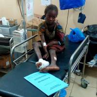 A wounded girl sits inside a hospital after a suspected Boko Haram attack on the edge of Maiduguri's inner city, Nigeria, Monday. | REUTERS