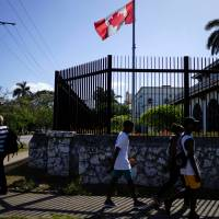 People pass by the Canadian Embassy in Havana Monday. | REUTERS