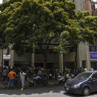 Venezuelan citizens wait outside the Chilean Consulate for information regarding a new visa program in Caracas on Monday. Chile's new visa for Venezuelans fleeing the country's economic collapse was greeted by confusion Monday, with hundreds lining up before dawn at the consulate in Caracas worried that they would be barred from entering the country. | BLOOMBERG