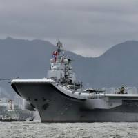 The Chinese aircraft carrier Liaoning is seen in waters off Hong Kong last July. The carrier conducted its first drills in the Pacific on Friday, according to the Defense Ministry in Tokyo. | KYODO