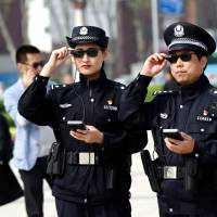 Police officers display AI-powered smart glasses in Luoyang, in China's Henan province, earlier this month. | REUTERS