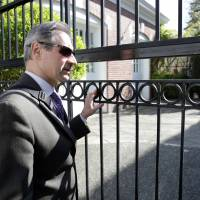 Nikolay Pukalov, head of the Consular Division from the Embassy of the Russian Federation, watches as members of the U.S. State Department gain access to the former residence of the Russian consul general in Seattle Wednesday.   REUTERS