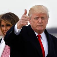 U.S. President Donald Trump gestures to the media as he arrives with his wife, Melania, and their son, Barron, at Andrews Air Force Base in Maryland on April 1. | REUTERS